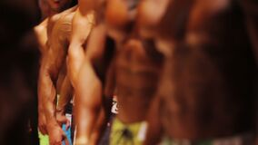 Strong muscular men defiling on stage at bodybuilding competition, healthy life