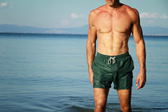 Strong muscular Men, perfect body, abs, six pack, sea, beach, swimwear Royalty Free Stock Photo