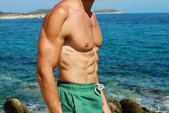 Strong muscular Men, scar, abs, six pack, sea, beach, swimwear Stock Images