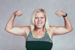 Strong muscular sporty woman flexing muscles. Strong excited muscular woman flexing her muscles. Young blond sporty female showing arms and biceps Royalty Free Stock Photos
