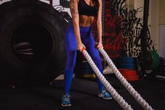 Athletic woman doing some crossfit exercises with a heavy rope royalty free stock photography