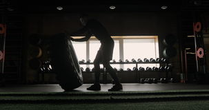 Strong muscular young man flipping tyre while exercising in CrossFit gym. stock video