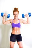 Strong muscular young woman lifting weights Stock Image