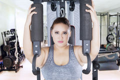 Strong overweight woman with shoulder press machine. Portrait of strong overweight woman looking at the camera while workout on a shoulder press machine in the stock images