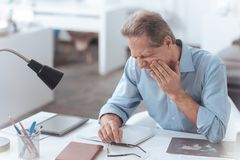 Unhappy adult man having a toothache. Strong pain. Unhappy nice adult man sitting at the table and holding his cheek while having a toothache Stock Images