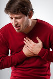 Strong pain. Young man in red sweater has a strong chest pain Stock Photo