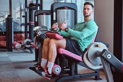 Strong pensive man is sitting on training apparatus in gym and doing legs exercises royalty free stock photo