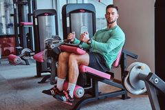 Strong pensive man is sitting on training apparatus in gym and doing legs exercises stock image