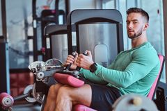 Strong pensive man is sitting on training apparatus in gym and doing legs exercises royalty free stock images