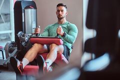 Strong pensive man is sitting on training apparatus in gym and doing legs exercises stock photography