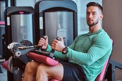 Strong pensive man is sitting on training apparatus in gym and doing legs exercises stock photo