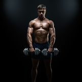 Strong and power bodybuilder doing exercises with dumbbell. Handsome power athletic guy bodybuilder doing exercises with dumbbell. Fitness muscular body on dark Royalty Free Stock Images