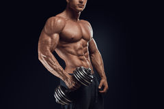 Strong and power bodybuilder doing exercises with dumbbell. Handsome power athletic man with dumbbell confidently looking forward. Strong bodybuilder with six Royalty Free Stock Photo