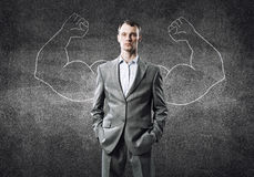 Strong and powerful. Businessman with strong arms drawn with chalk behind his back stock image