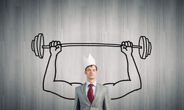 Strong and powerful. Young man with drawn strong hands lifting barbell stock image