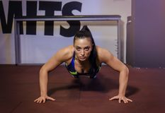 Strong powerful young woman doing push ups royalty free stock photo