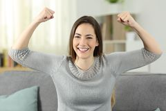 Strong and proud woman gesturling looking at you. Sitting on a couch in the living room at home Stock Photo