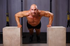 Strong ripped bald man work out. Bodybuilder doing push-ups in g stock photography