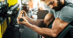Strong ripped man training in gym. Strong ripped man training bicepses in gym stock image