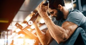 Strong ripped man training in gym. Strong ripped man training bicepses in gym stock photography