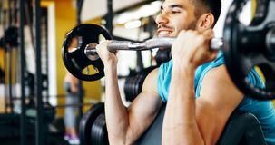 Strong ripped man training in gym. Strong ripped man training bicepses in gym royalty free stock photography