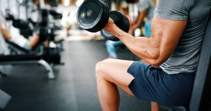Strong ripped man training in gym to reach goals. Strong ripped men training bicepses in gym royalty free stock photography