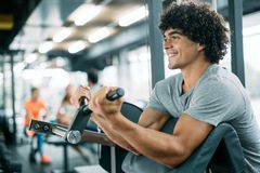 Strong ripped man training in modern gym. Strong ripped men training bicepses in gym stock images