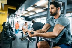 Strong ripped man training in modern gym royalty free stock images