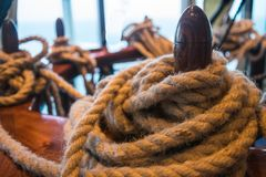 Strong rope around post, nautical. Twisted, coiled roped wrapped around anchor post. Nautical, western, natural, representing work tools stock photography