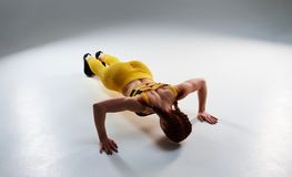 Strong rude woman doing push-ups. In studio Royalty Free Stock Photography