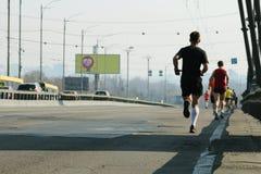 Strong runners running on city bridge road. Running on city road. Marathon running in the morning. Athletes runner feet running. stock photography