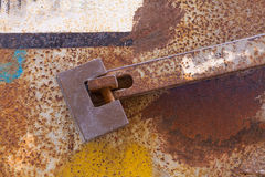 Strong rusty padlock with heavy iron bar locking metal door Stock Photos