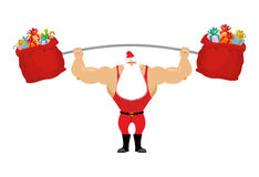 Strong Santa Claus holding barbell and gift bag.  Royalty Free Stock Photo