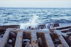 Strong sea wave crashing on the rocky shores. Selective focus; toned image Royalty Free Stock Photos