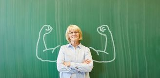 Strong senior teacher with chalk muscles. In front of chalkboard Royalty Free Stock Image