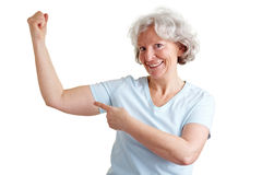 Strong senior woman doing fitness. Elderly happy senior woman doing fitness exercises and showing her muscles Royalty Free Stock Photo