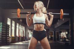 Strong sexy athletic young woman working out in gym. Beautiful strong sexy athletic muscular young caucasian fitness woman workout training in the gym on diet royalty free stock photography