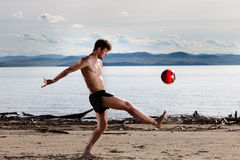 Strong sexy male kick red ball Royalty Free Stock Images