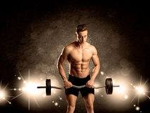 Strong sexy male working out. An attractive muscular guy working out with weights and showing naked upper body with illustrated lights and bokeh concept Royalty Free Stock Images