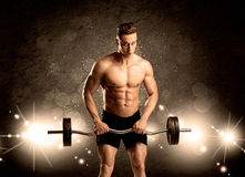 Strong sexy male working out. An attractive muscular guy working out with weights and showing naked upper body with illustrated lights and bokeh concept Stock Photography