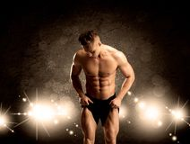 Strong sexy male working out. An attractive muscular guy working out with weights and showing naked upper body with illustrated lights and bokeh concept Royalty Free Stock Photos