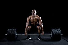 Strong sexy man deadlifts a lot of weight Royalty Free Stock Photography