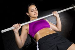 Strong woman bench presses. A strong woman bench presses weight stock photos