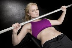 Strong sexy woman bench presses Royalty Free Stock Photo