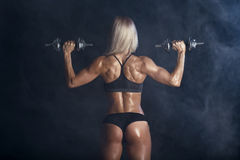 Strong woman is training with barbells. Strong blonde girl is training with barbells on smoke background back view stock photography
