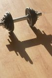 Strong shadow. A dumbell with its shadow stock images