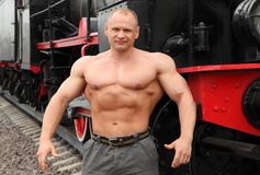 Strong shirtless man against locomotive stock photo