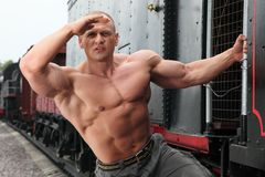 Strong shirtless man keeps watch on locomotive Stock Image
