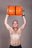 Strong shirtless man lifting a gas bottle Royalty Free Stock Image