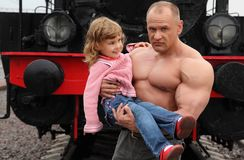 Strong shirtless man with little girl on hands Stock Images